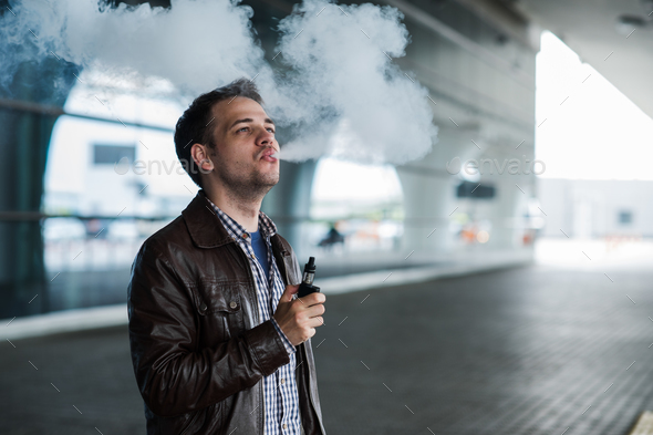 Young traveller man smoking an electronic cigarette outdoor near the airport terminal - Stock Photo - Images