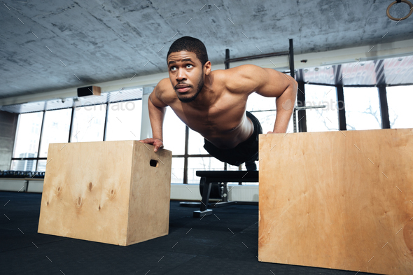 Healthy fitness man doing push-ups in the gym - Stock Photo - Images