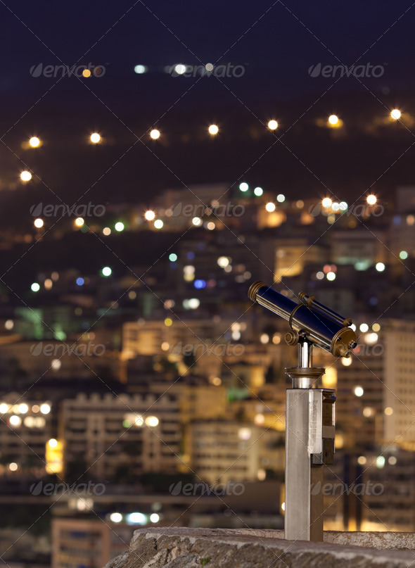night city (with a telescope in the foreground, focus is on the - Stock Photo - Images