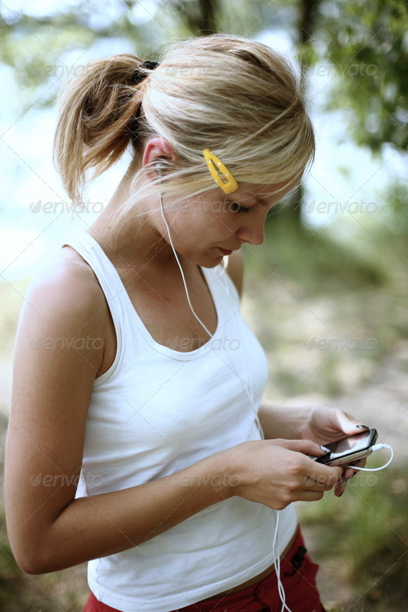 Portrait of a teenager wearing headphones and listening to music on her mp3 player - Stock Photo - Images