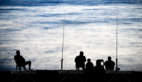 Sea/Ocean fishing - fishermen sitting by the sea/ocean in darkne - Stock Photo - Images