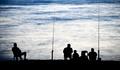 Sea/Ocean fishing - fishermen sitting by the sea/ocean in darkne