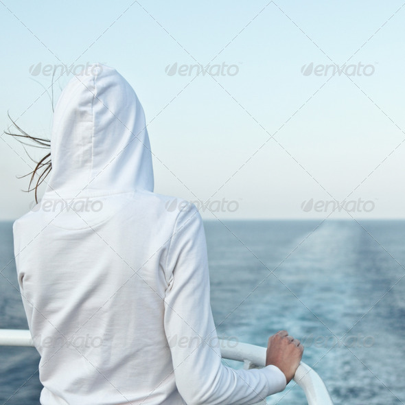 Young woman looking at the ocean from a fast going liner - Stock Photo - Images