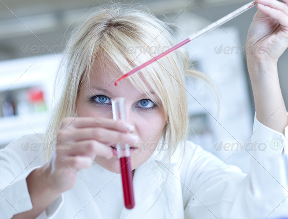 Closeup of a female researcher carrying out experiments in a lab - Stock Photo - Images