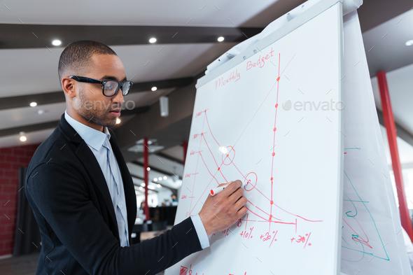 Businessman making presentation on the flipchart - Stock Photo - Images