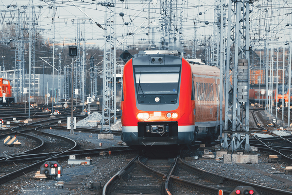Railway station with modern red commuter train at sunset - Stock Photo - Images