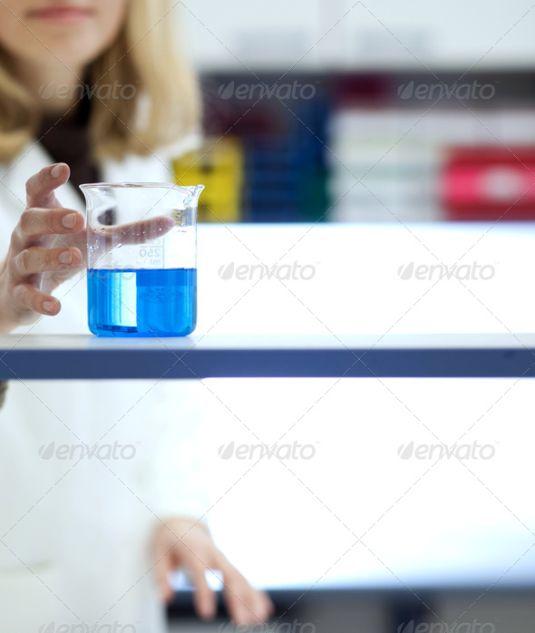female researcher carrying out research/experiments in a chemist - Stock Photo - Images
