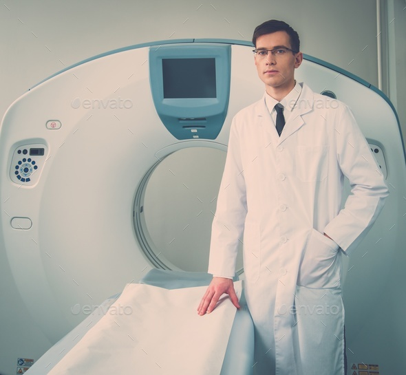 Young doctor standing near computed tomography scanner in a hospital - Stock Photo - Images