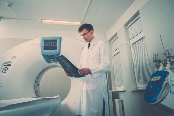 Doctor looking at the computed tomography results - Stock Photo - Images