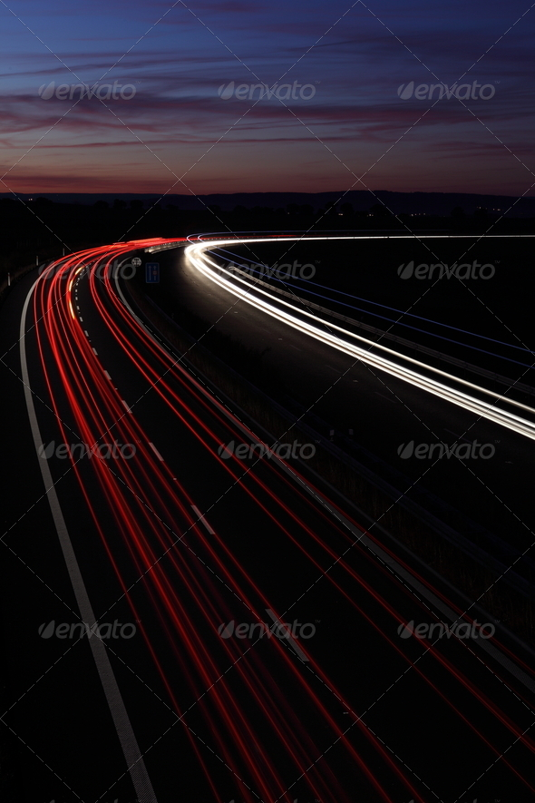 Cars in a rush moving fast on a highway (speedway) at dusk - Stock Photo - Images