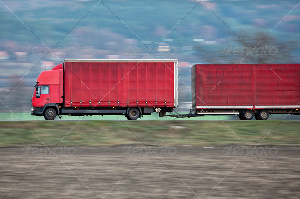 red camion/truck goes fast on a road (panned image - motion blur - Stock Photo - Images