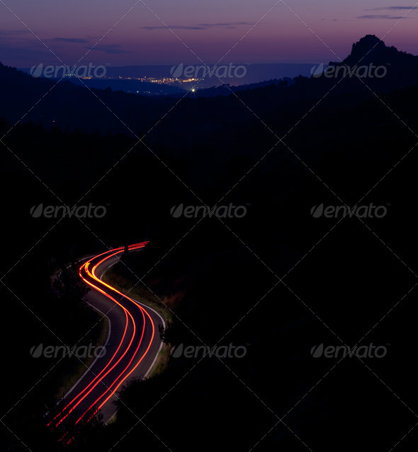 car moving fast on a winding road  at dusk - Stock Photo - Images