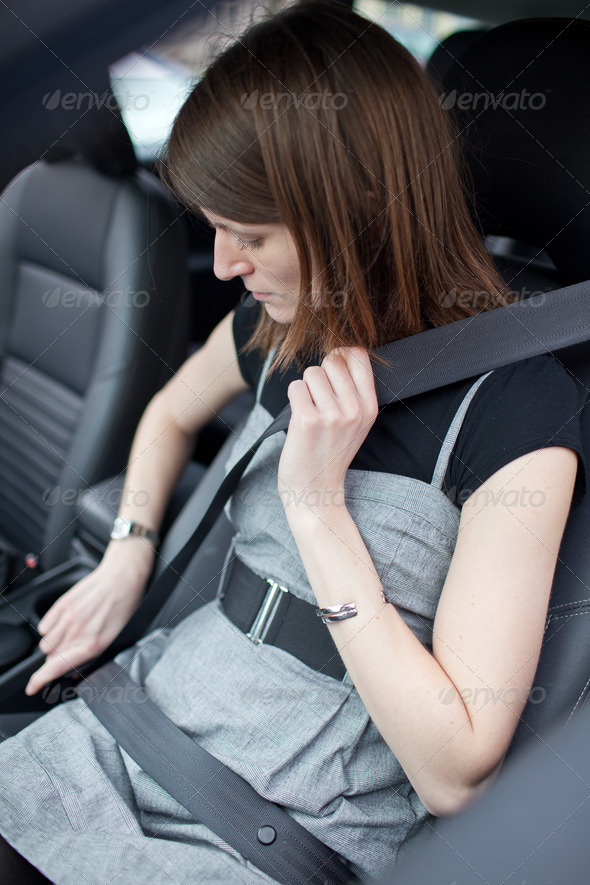 Road safety concept - Pretty young woman fastening her seat belt - Stock Photo - Images