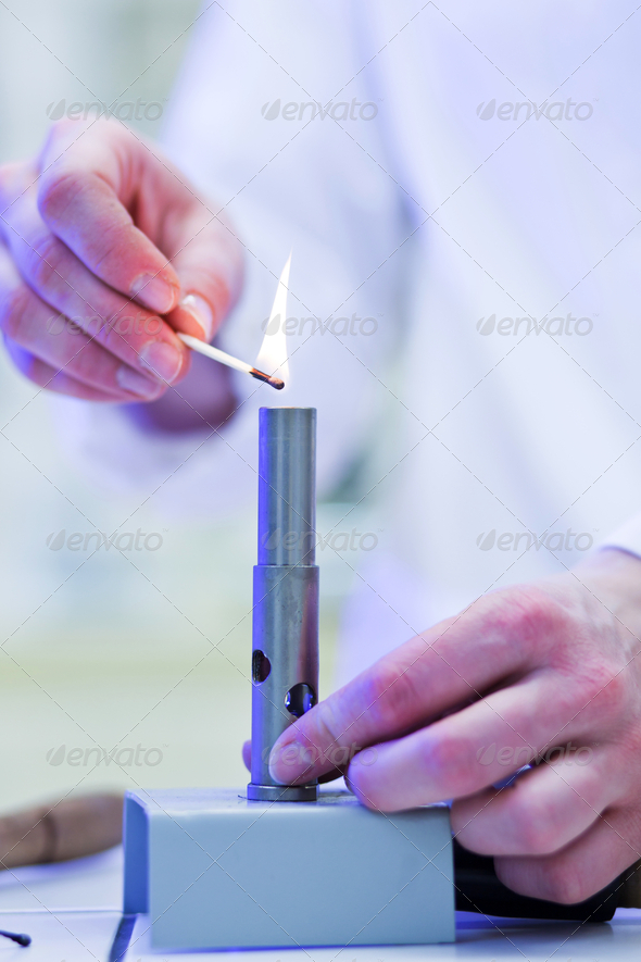 pretty, young female researcher lighting up a burner in a lab (s - Stock Photo - Images
