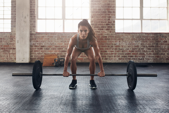 Female performing deadlift exercise with weight bar - Stock Photo - Images