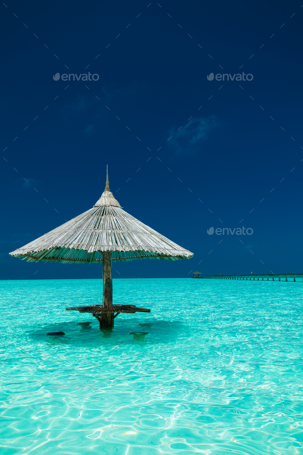 Bamboo beach umbrella with bar seats in the water of an island - Stock Photo - Images