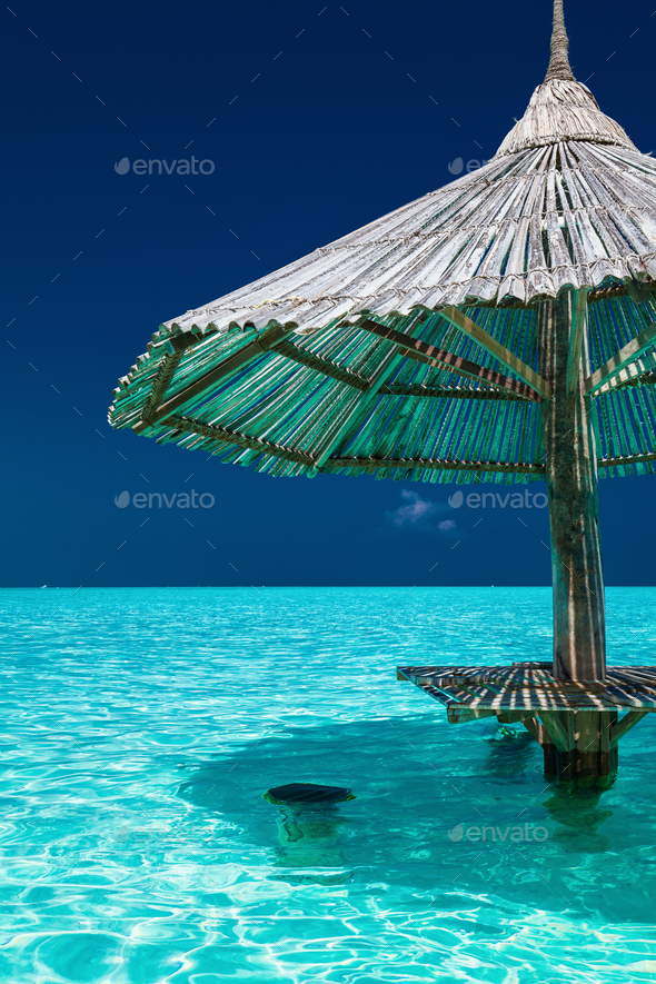 Bamboo beach umbrella in the water of tropical island - Stock Photo - Images