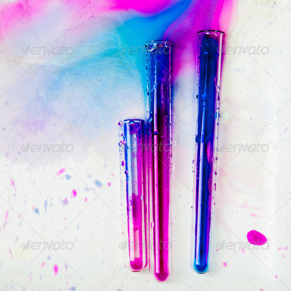 test tubes with colorful substances spilled on a white table in - Stock Photo - Images