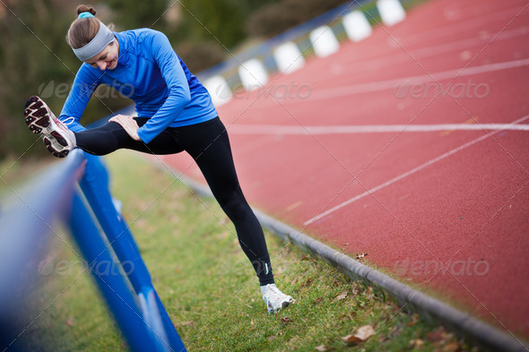Young woman stretching before her run - Stock Photo - Images