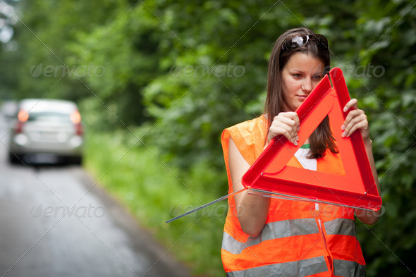Young female driver wearing a high visibility vest, calling the - Stock Photo - Images