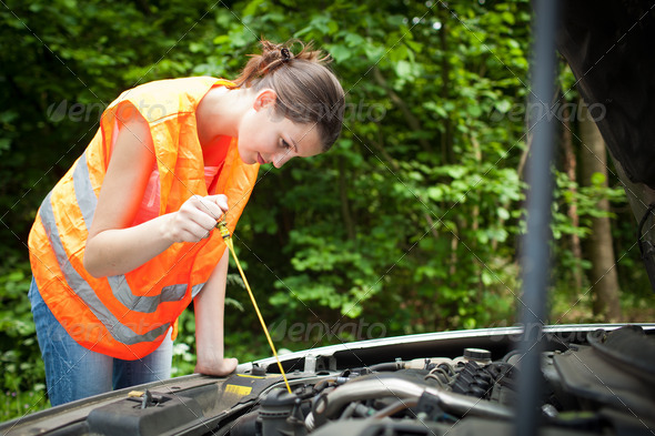 Young female driver wearing a high visibility vest, bending over - Stock Photo - Images