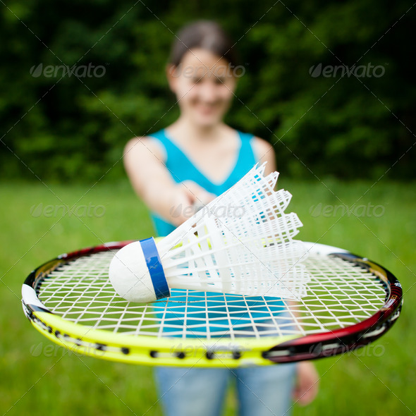 Pretty, young woman playing badminton in a city park on a lovely - Stock Photo - Images