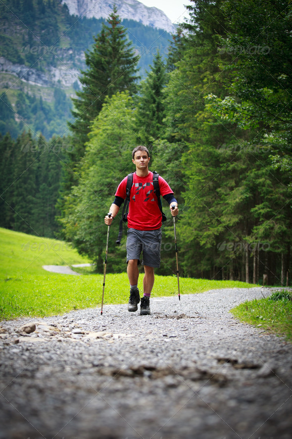 active handsome young man nordic walking/hiking in mountains, en - Stock Photo - Images