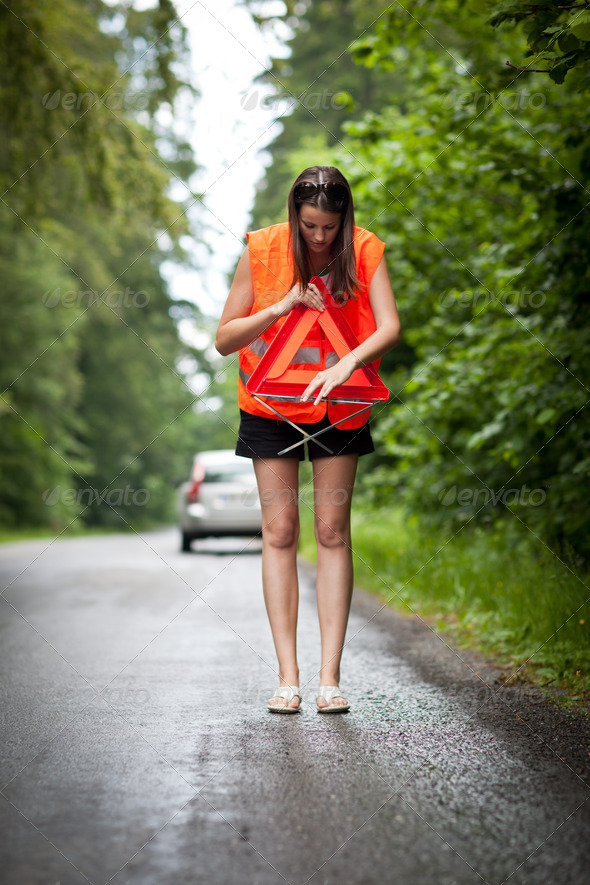 Young female driver wearing a high visibility vest/safety vest, - Stock Photo - Images