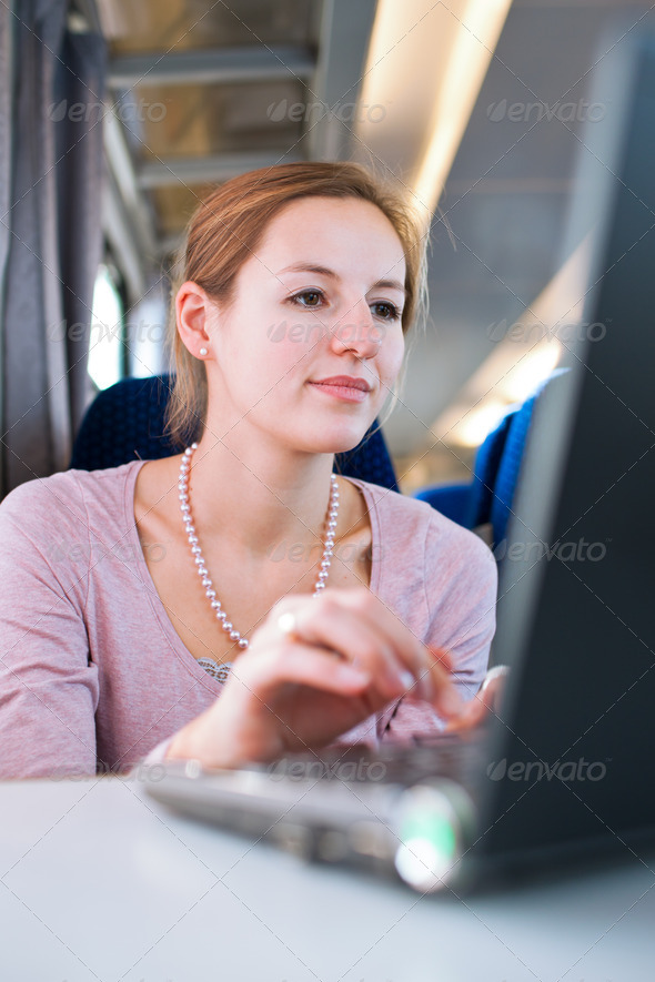 Young woman using her laptop computer while on the train (shallo - Stock Photo - Images