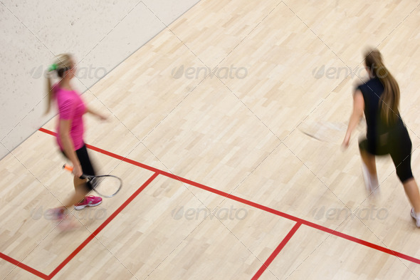 Two female squash players in fast action on a squash court (moti - Stock Photo - Images