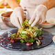 Hands touch salad on plate. - PhotoDune Item for Sale