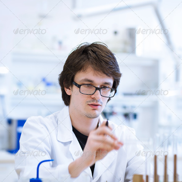young, male researcher/chemistry student carrying out scientific - Stock Photo - Images