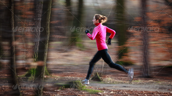 Young woman running outdoors in a city park on a cold fall/winte - Stock Photo - Images