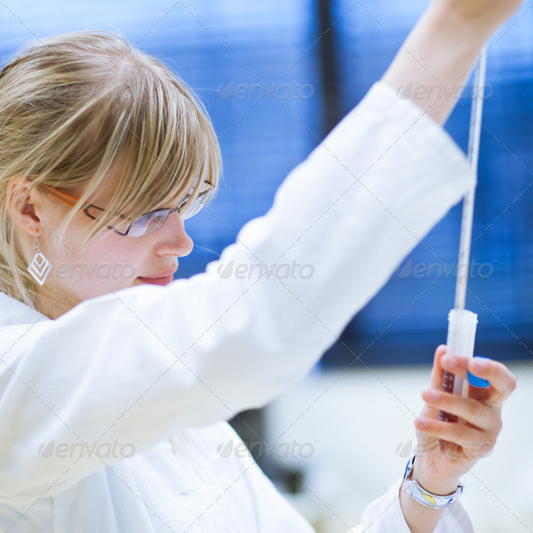 female researcher carrying out research experiments in a chemist - Stock Photo - Images