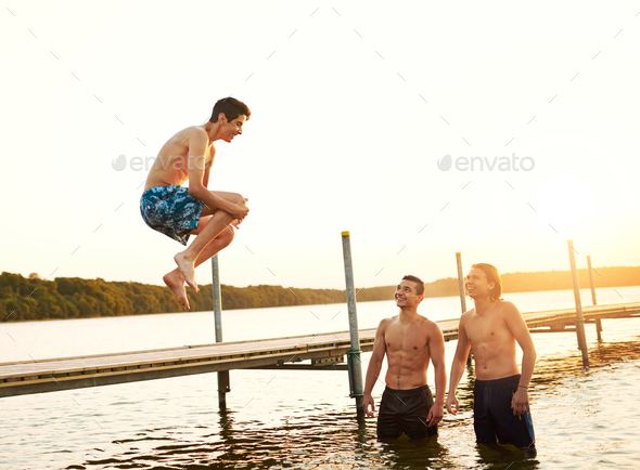 Teenage boy jumping into a lake - Stock Photo - Images