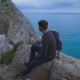 Young Hipster Guy Sitting On The Rock Mountains Near Sea, Man With a Rucksack On His Back - VideoHive Item for Sale