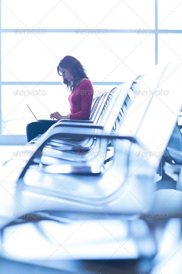 Young woman at the airport, working on a laptop and waiting for - Stock Photo - Images
