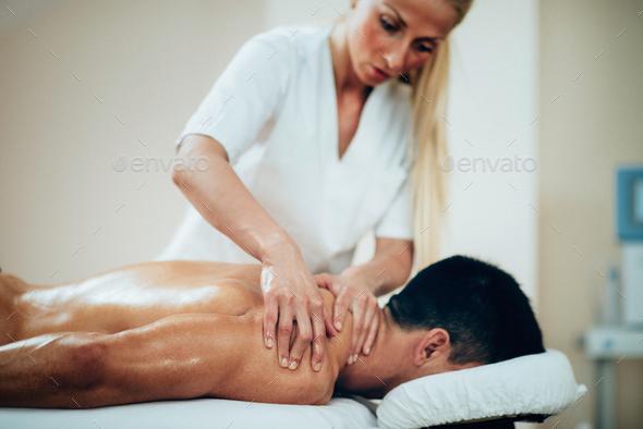 Sports massage. Therapist doing shoulder massage - Stock Photo - Images