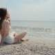 Girl Sits On Beach And Messages On Her Phone - VideoHive Item for Sale