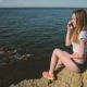 Girl Sitting On The Rocks And Talking On The Phone, Laughing And Smiling - VideoHive Item for Sale