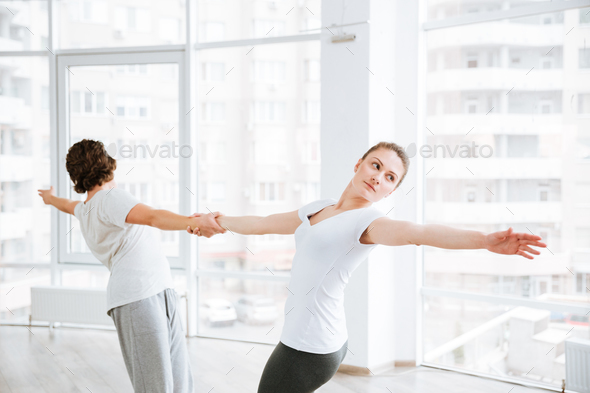 Beautiful young woman practicing yoga with partner in studio - Stock Photo - Images