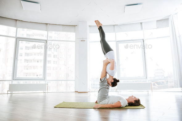 Beauiful couple practicing acro yoga on green mat - Stock Photo - Images