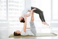 Peaceful couple balancing and doing acro yoga in studio