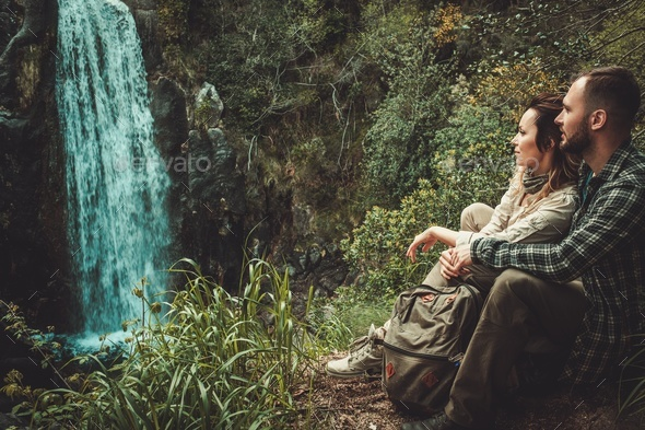 Beautiful woman hiker sitting near waterfall in deep forest. - Stock Photo - Images