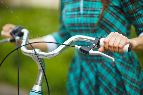 Girl walking with her bicycle outdoors - Stock Photo - Images