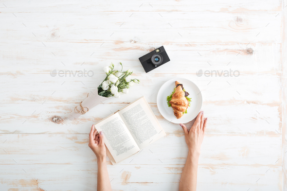 Female hands holding book on the wooden desk - Stock Photo - Images