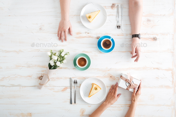 Hands of woman giving present to man on wooden table - Stock Photo - Images