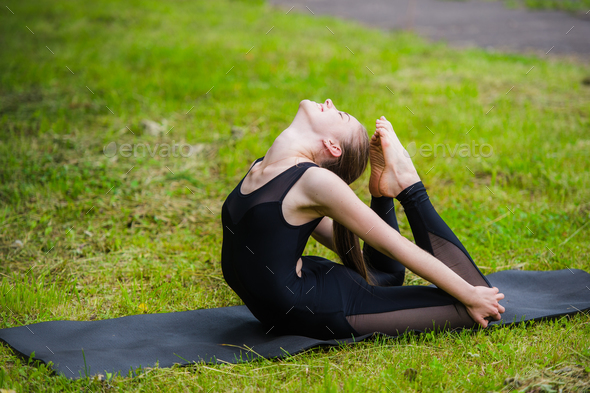 Young woman doing gymnastics yoga and stretching in the city park on sunset - Stock Photo - Images