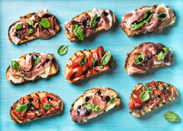 Brushetta snacks for wine. Variety of small sandwiches on turquoise blue backdrop - Stock Photo - Images