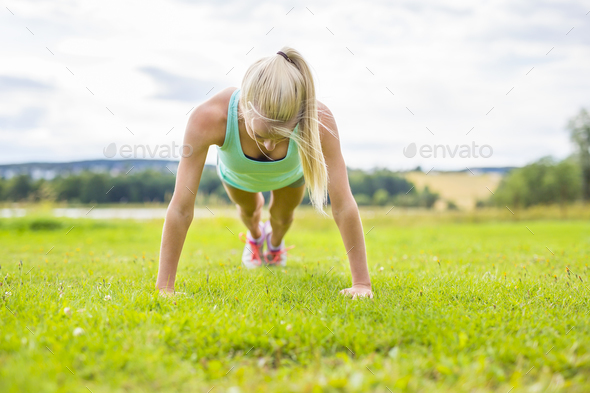 Young woman doing push-ups in the park - Stock Photo - Images